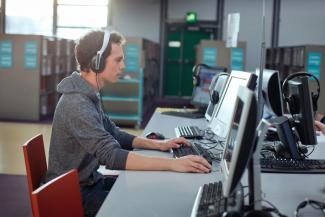 Man wearing headset and focused on on a computer-based training.